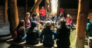 Indigenous tour guide educating a group of visitors in the sweat lodge at Xwisten Experience Tours